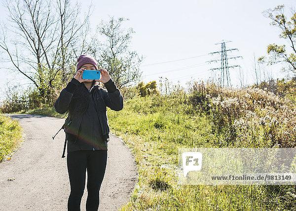 Junge Frau fotografiert auf dem Smartphone