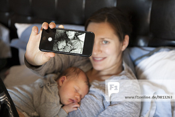 Baby girl sleeping on mother's chest,  while mother takes self portrait of them both,  using smartphone