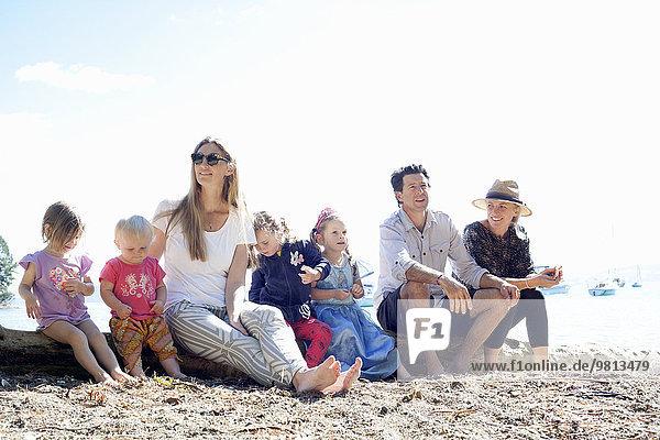 Familien und Töchter auf Baumstamm am Strand  Neuseeland