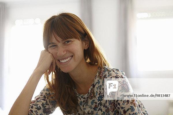 Porträt einer lächelnden mittleren erwachsenen Frau in der Küche
