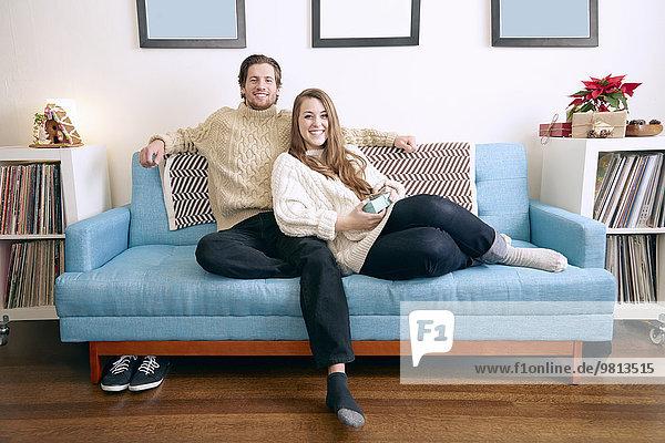 Porträt eines jungen Paares auf dem Wohnzimmersofa mit Weihnachtsgeschenk