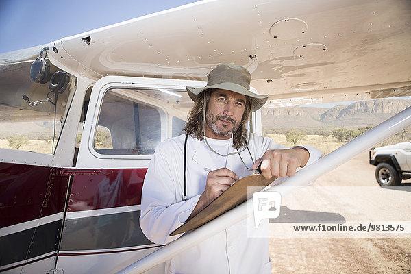 Medizinisches Personal schreibt auf Klemmbrett neben dem Flugzeug  Wellington  Western Cape  Südafrika