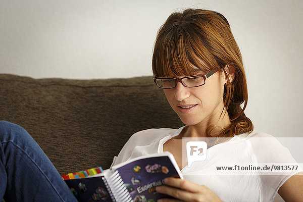 Mid adult woman reading filofax on sitting room sofa