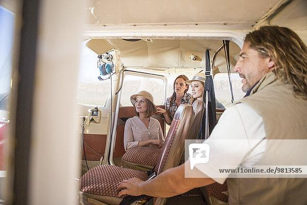 Touristen  die die Steuertafeln im Flugzeug betrachten