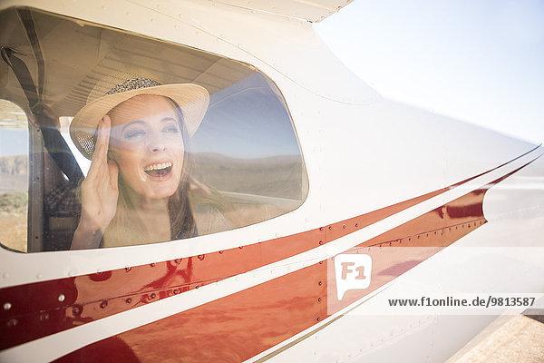 Tourist winkt aus dem Flugzeug heraus