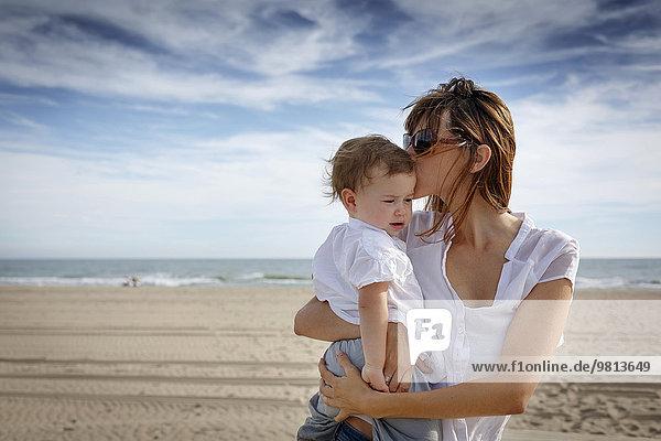 Mittlere erwachsene Frau küssend Kleinkind Tochter am Strand  Castelldefels  Katalonien  Spanien