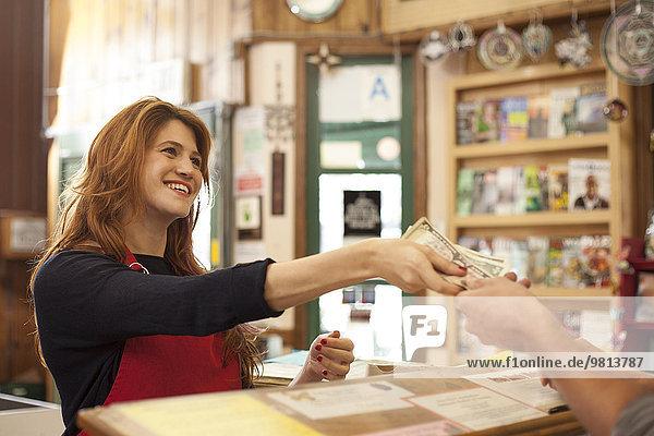 Verkäuferin bei der Barzahlung im Naturkostladen