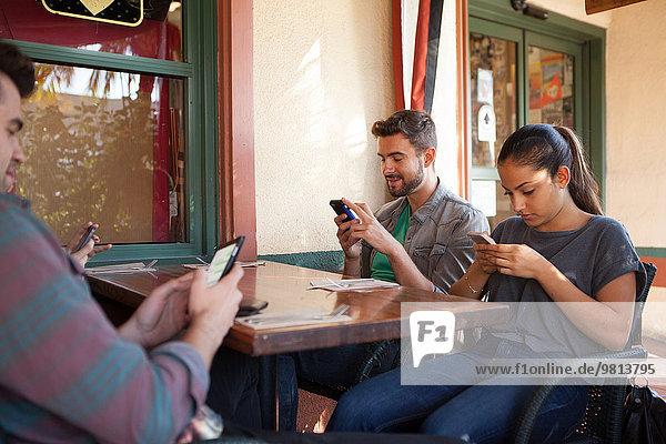 Vier Freunde texten individuell auf Smartphones im vegetarischen Restaurant