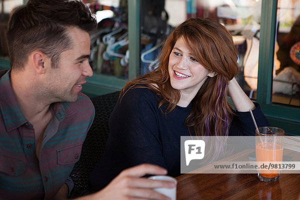 Male and female friends chatting in vegetarian restaurant