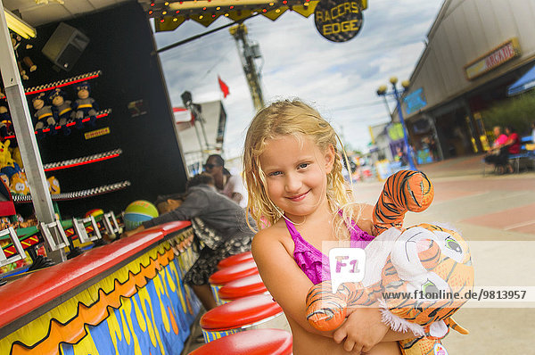 Portrait of girl carrying prize tiger toy at fairground stall