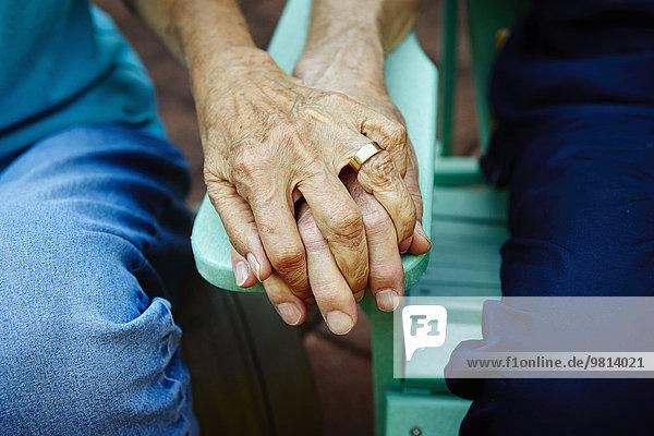 Ausschnitt aus der Nähe eines älteren Ehepaares  das sich auf der Parkbank hält.