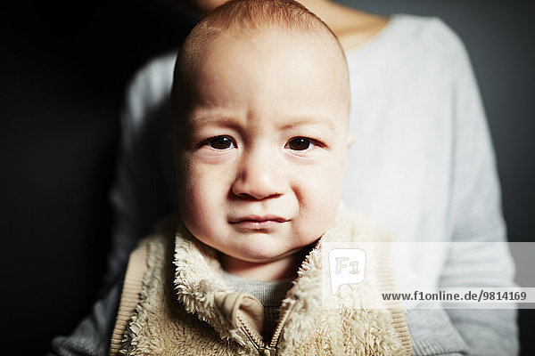 Close up portrait of cute baby boy in front of mother