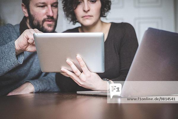 Paar am Tisch sitzend mit Laptop und digitalem Tablett