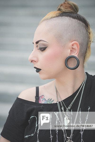 Porträt einer jungen Punkerin mit Piercings und rasiertem Kopf