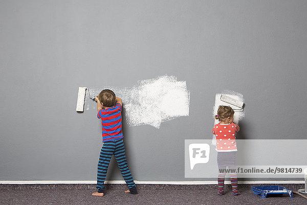 Rückansicht von Bruder und Kleinkind Schwester Malerei Wand