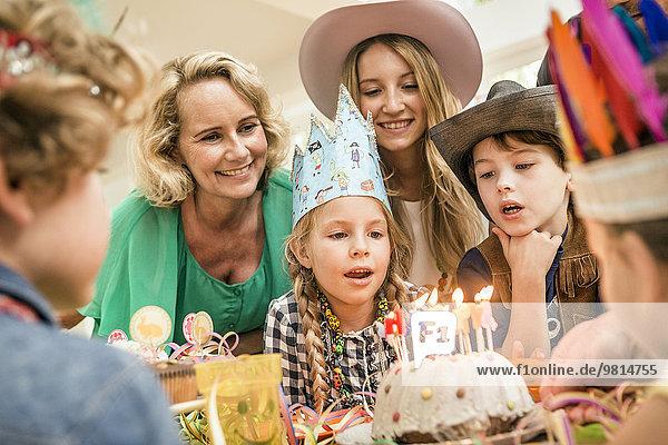 Drei-Generationen-Familie bei der Kindergeburtstagsparty beim Ausblasen von Kerzen