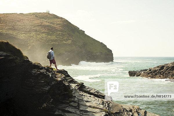 Mittlerer Erwachsener Mann  der von einer Felsenklippe  Boscastle  Cornwall  UK  hinausblickt.