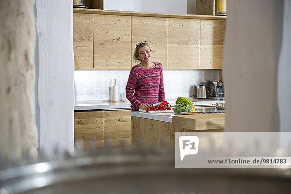 Porträt einer reifen Frau in der Küche beim Zubereiten von Gemüse