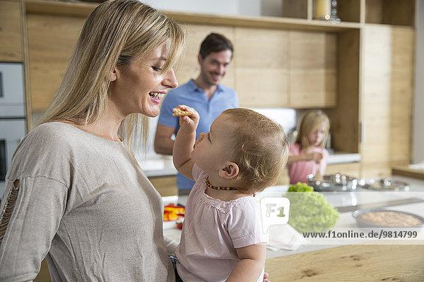 Weibliches Kleinkind füttert Mutter in der Küche