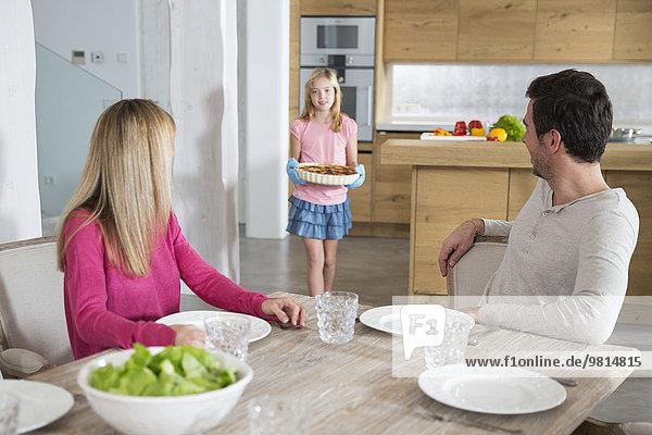 Mädchen mit hausgemachter Gemüse Quiche für Eltern in der Küche