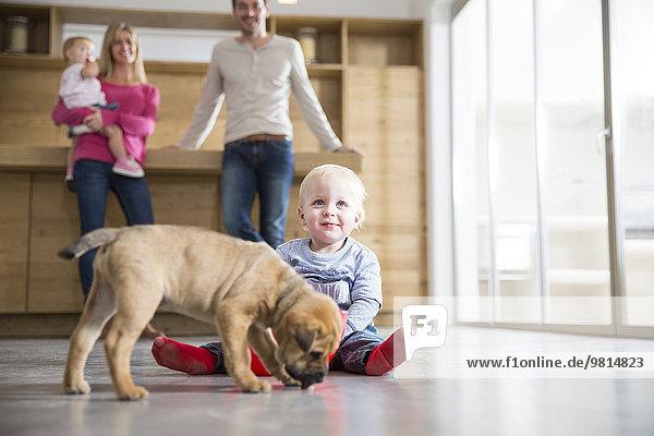 Familie beobachtet männliches Kleinkind mit Welpe auf dem Esszimmerboden