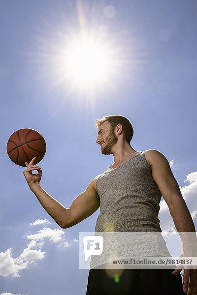 Junger Basketballspieler beim Balancieren und Spinnen am Finger