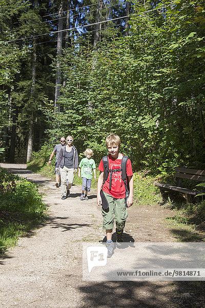 Eltern und Kinder wandern auf Waldweg  Berchtesgaden  Obersalzberg  Bayern  Deutschland
