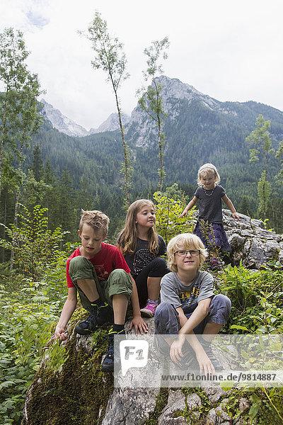Brüder und Schwestern auf Felsformation im Wald  Zauberwald  Bayern  Deutschland