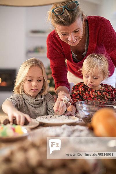 Mutter und Töchter backen zu Weihnachten