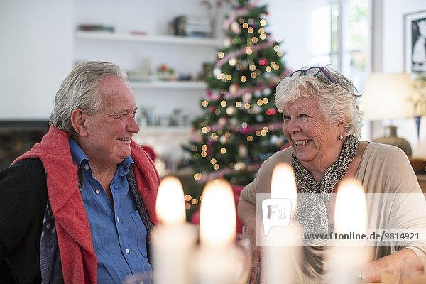 Seniorenpaar im Gespräch am weihnachtlichen Mittagstisch