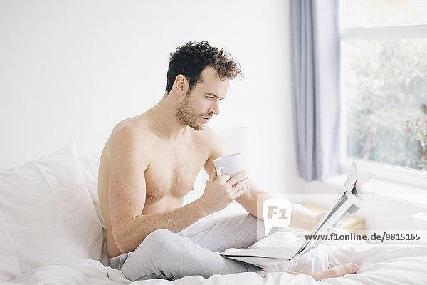 Junger Mann im Bett liegend  Kaffee trinkend und Zeitung lesend