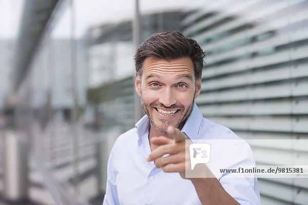 Portrait eines reifen Geschäftsmannes außerhalb des Bürogebäudes mit dem Fingerzeig