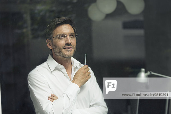 Porträt eines Geschäftsmannes  der aus dem Bürofenster blickt.