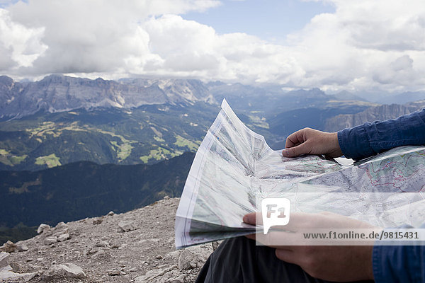 Cropped shot of male hiker on top of mountain holding map  Peitlerkofel  South Tyrol  Italy