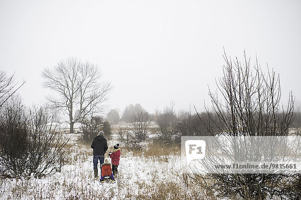 Father and daughters in rural scene in winter