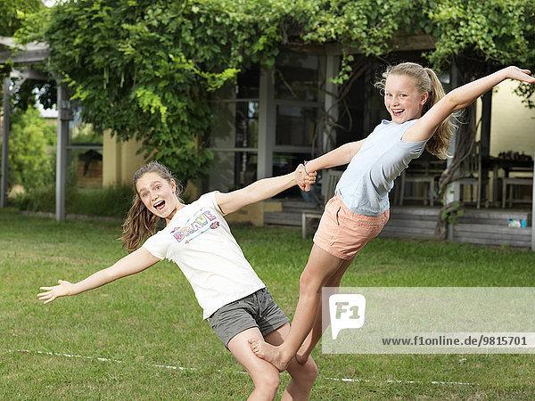 Zwei Schwestern bei der Akrobatik im Garten