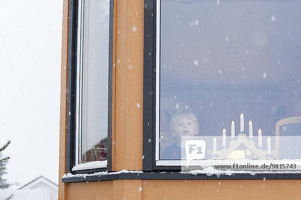 Junge wartet hinter dem Fenster