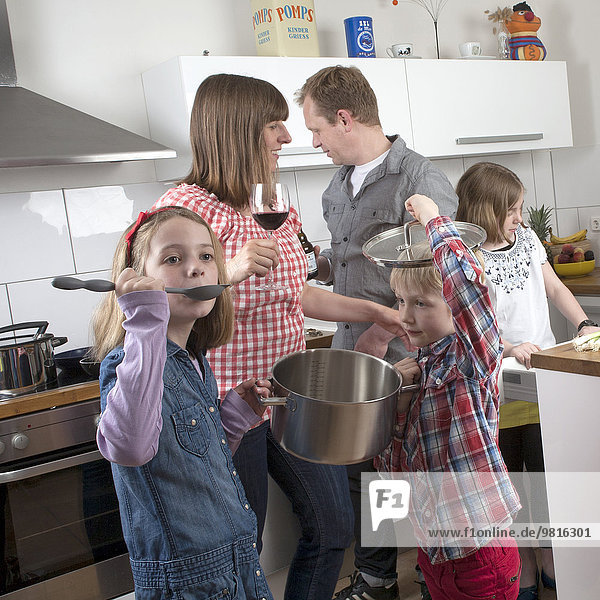 Family with three children cooking together
