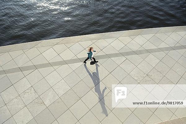 Junge Frau beim Spaziergang an der Uferpromenade