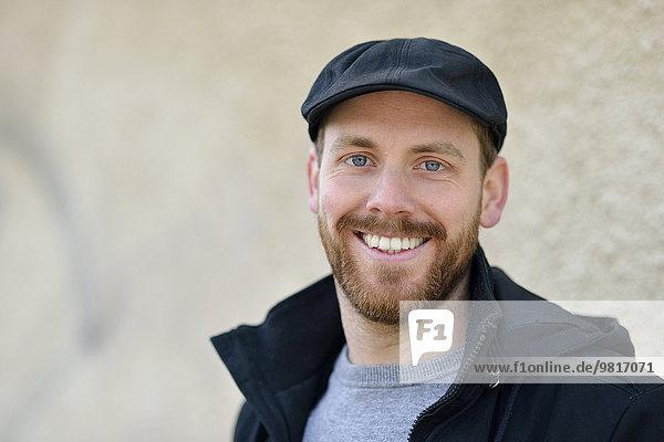 Portrait eines lächelnden jungen Mannes mit Mütze