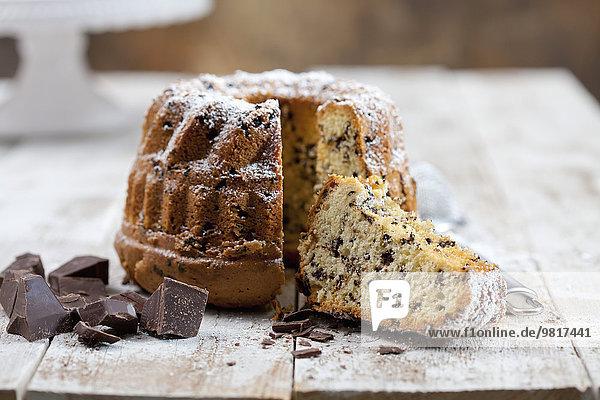 Geschnittener Schokoladenkuchen mit Puderzucker und Schokostückchen auf Holz