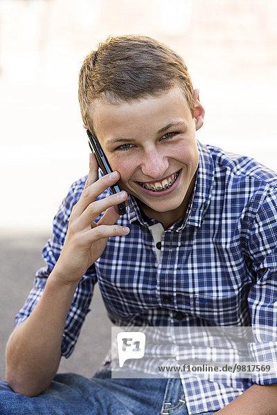 Porträt des lächelnden Teenagers mit Spange am Telefon