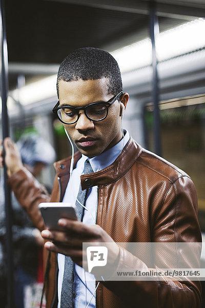 Portrait eines Geschäftsmannes mit Smartphone und Kopfhörer  der Musik in der U-Bahn hört.