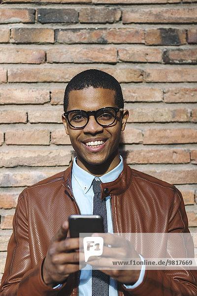Porträt eines lächelnden Geschäftsmannes mit Smartphone in Lederjacke und Brille