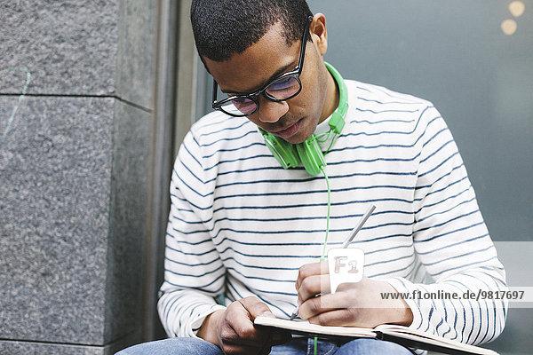 Junger Mann mit grünen Kopfhörern sitzt draußen und schreibt etwas in sein Notizbuch.