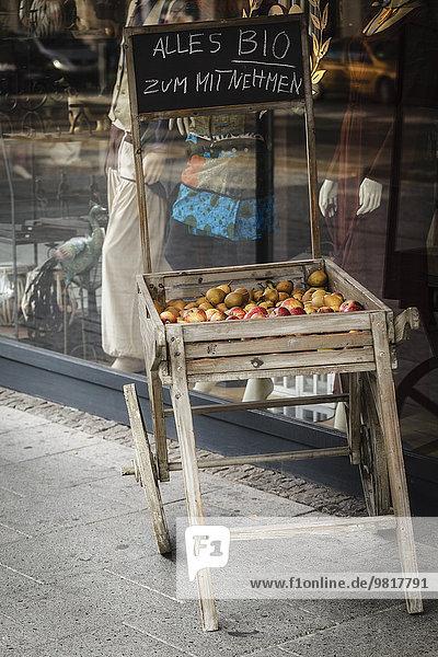 Deutschland  Braunschweig  Holzkiste mit Bio-Früchten zum Mitnehmen vor einer Schaufensterdekoration