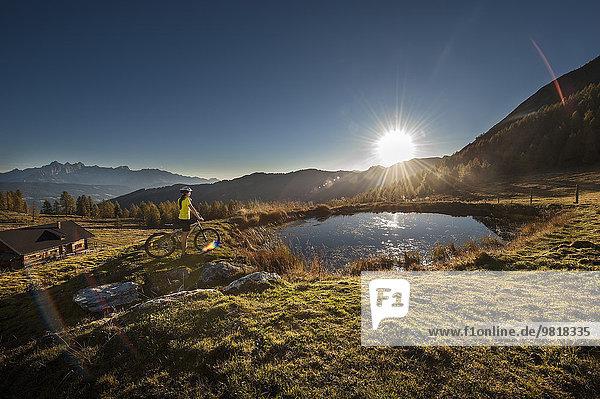 Österreich  Altenmarkt-Zauchensee  junge Frau mit Mountainbike in den Bergen bei Sonnenaufgang