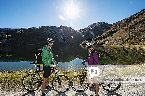 Österreich  Altenmarkt-Zauchensee  junges Paar mit Mountainbikes am Bergsee