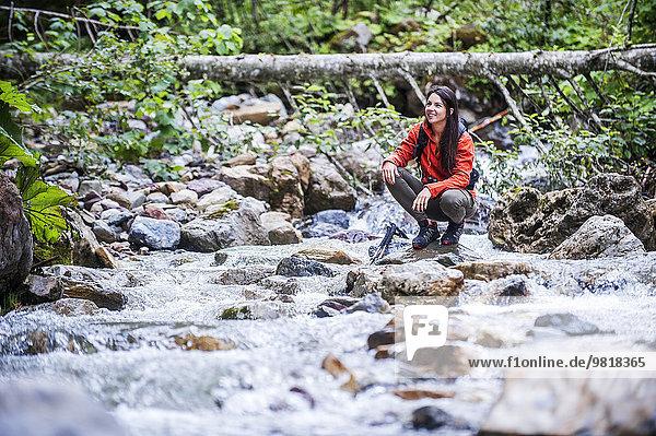Austria  Altenmarkt-Zauchensee  young female hiker crouching at a river