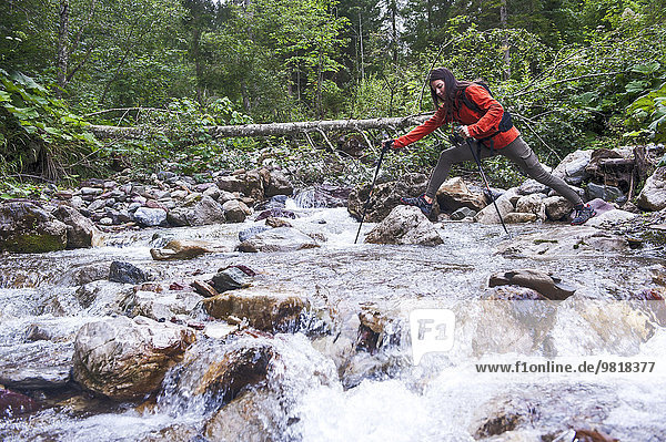 Österreich  Altenmarkt-Zauchensee  junge Wanderin überquert einen Fluss